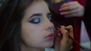 Close up shot of make up artist applying glitter eyeshadows slow motion
