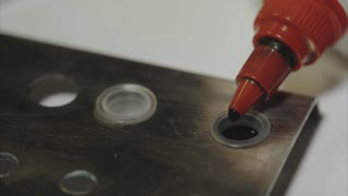 Close up shot of tattoo master dropping ink into the container