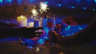 Couple toasting with champagne christmas scene and sparkler