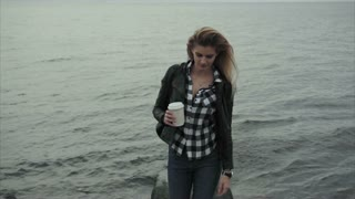 Cute young blond woman holding a cup of coffee in her hands near the sea
