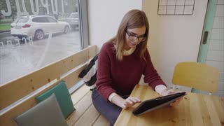 Cute young woman student with tablet in cafe