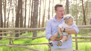 Dad holding kissing his sweet daughter baby with a bow on her head, baby laughs