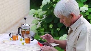 Eldary man using digital tablet in summer garden table with tea