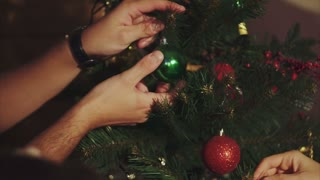 Family decorate christmas tree close up