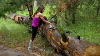 Fitness girl in the forest. Practice exercises on the old tree. Slow motion.