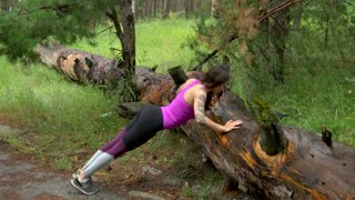 Fitness girl in the forest. Practice Push ups exercise on the old tree.