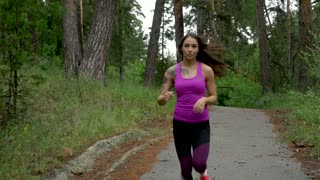 fitness workout outdoors. Sport woman running through the woods. slow motion.