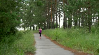 Girl runs through park in the morning, slow motion, Sony camera