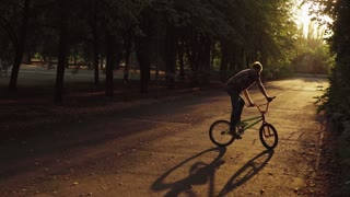Guy dressed in a free style riding in the park with tall trees on a bicycle BMX.