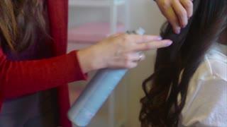 Hairstylist sprays hairspray on brunette making hair-do