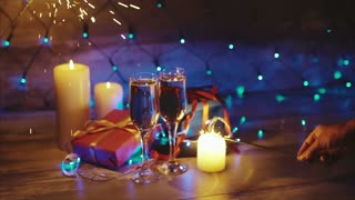 Hands with sparklers on the background of Christmas gifts candles and champagne