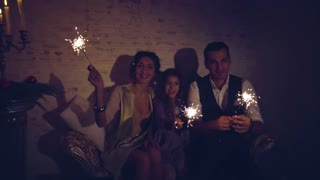 Happy family and bengal fire or sparklers lights in dark room at christmas eve