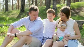 Happy family of four on picnic at summer sunny day