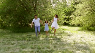 Happy family running in a beautiful park while holding hands with eachother