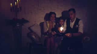 Happy family with daughter lighting sparklers in the dark at christmas eve
