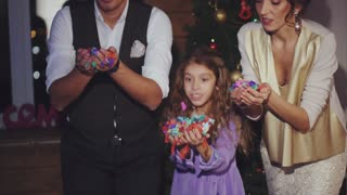 Happy mom, dad and daughter blowing colorful confetti celebration of Christmas