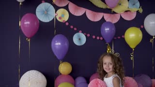 Little cute girl celebrating and sitting around her birthday party decorations