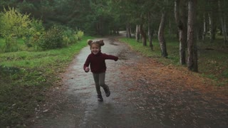 Little pretty girl running in the autumn park. Concept of happy childhood.