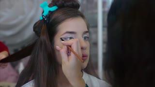 Make up artist applying eyeshadow while hairdresser making hair-do.