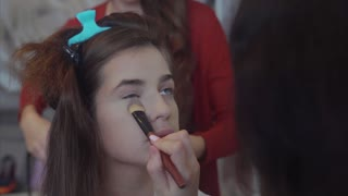 Make up artist applying foundation or concealer while hairstylist making hair-do