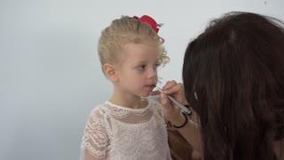 Make up artist applying lip gloss to little cute girl