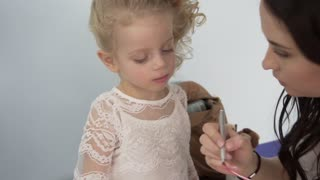 Make up artist applying lipstick to little pretty girl