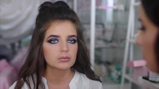 Make up artist applying powder on model face