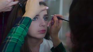 Make up artist applying shade for eyebrows while hairdresser making hair-do