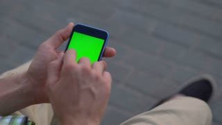 Man hand using smartphone with green screen