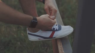 Man runner tying shoelace in the nature