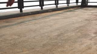 Mans legs roller skating inline close up on the asphalt sunset
