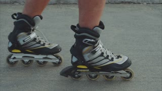 Mans legs roller skating inline close up on the asphalt
