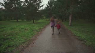 Mother and daughter running in the autumn park