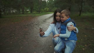 Mother and son making selfie in the autumn park