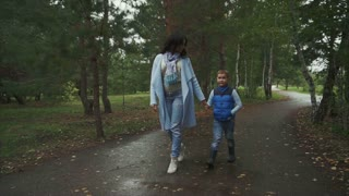 Mother and son walking in the autumn park