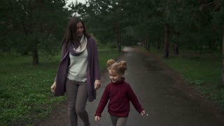 Mother play with her daughter in the autumn park