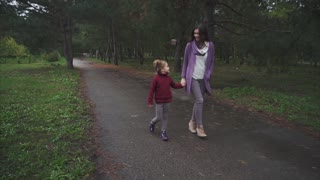 Mum and daughter walking in the autumn park