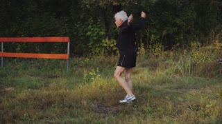 Old man senior does morning warm up exercises before jogging