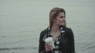 Portrait of attractive young blond woman with a cup of coffee near the sea