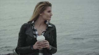 Portrait of beautiful young blond woman with a cup of coffee near the sea
