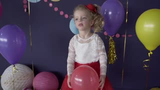 Portrait of little cute girl throwing red balloon on her birthday party