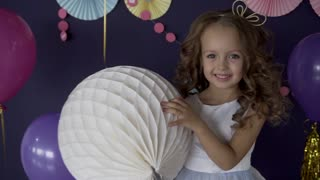 Portrait of pretty baby girl holding big white balloon concept of birthday party
