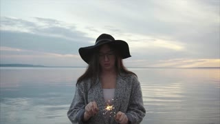Pretty happy woman lights sparklers on the sea coast at sunset