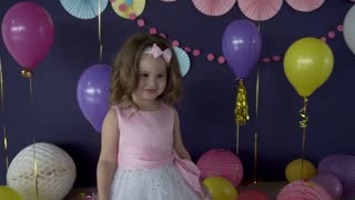 Pretty little baby girl laughing and blowing a kiss on her birthday party