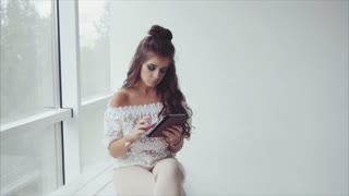 Pretty woman brunette using her tablet on white background near the window