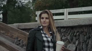 Pretty woman with a cup of coffee outdoor. Beautiful girl enjoying her morning.
