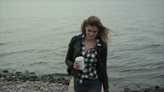 Pretty young blond woman holding a cup of coffee in her hands near the sea