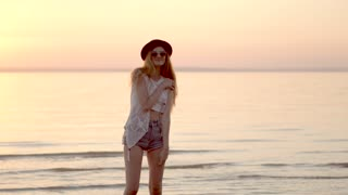Pretty young blonde girl in hat posing on background of ocean and golden sunset
