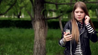 Pretty young girl listening music in headphones in the park