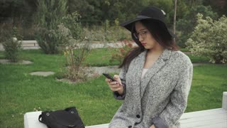 Pretty young woman in black hat and glasses using smartphone in city park